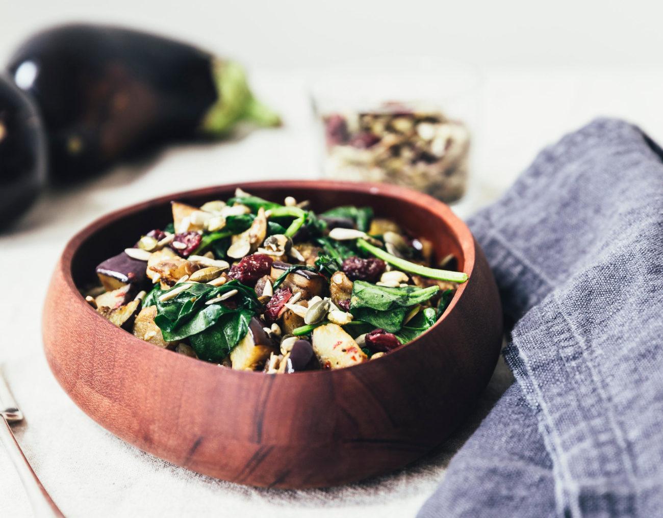 Speltsalat med stegte auberginer, kerner og tranebær samt spinat
