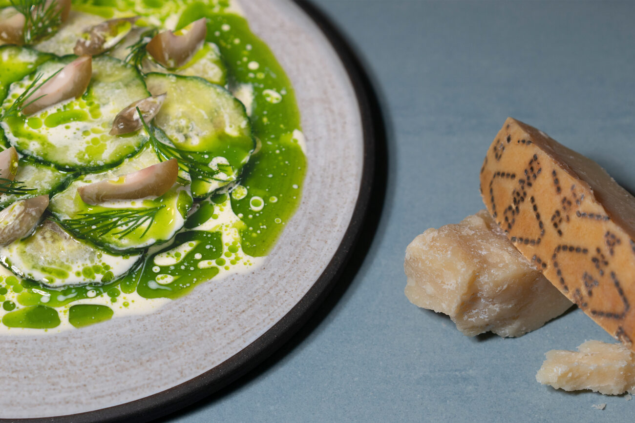 Røget laks, agurk, umoden fersken, ramsløgskapers, dild og ostesauce af Grana Padano skilt med dildolie