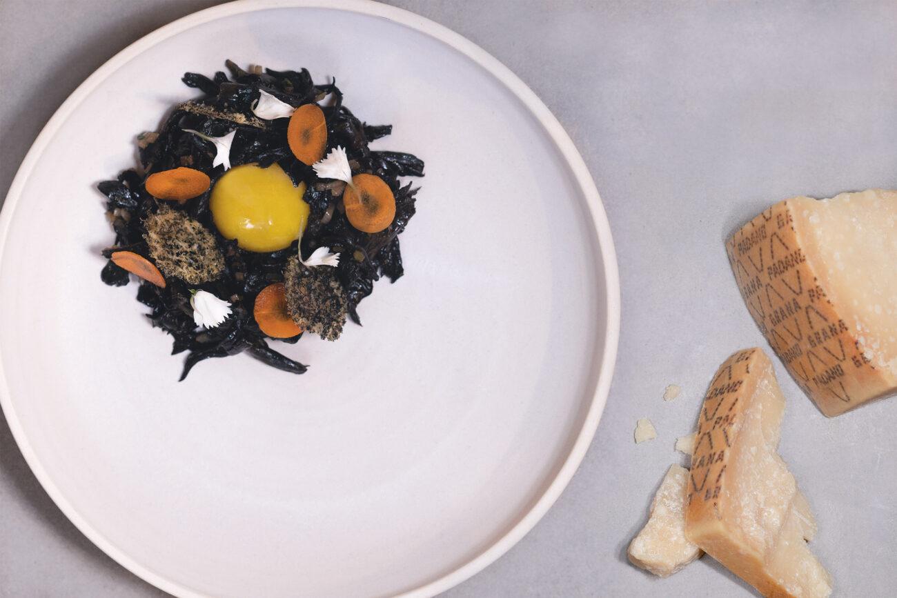Sorte trompetsvampe, trøffelkompot, confiteret æggeblomme, forkullet hvidløg og ostekiks af Grana Padano