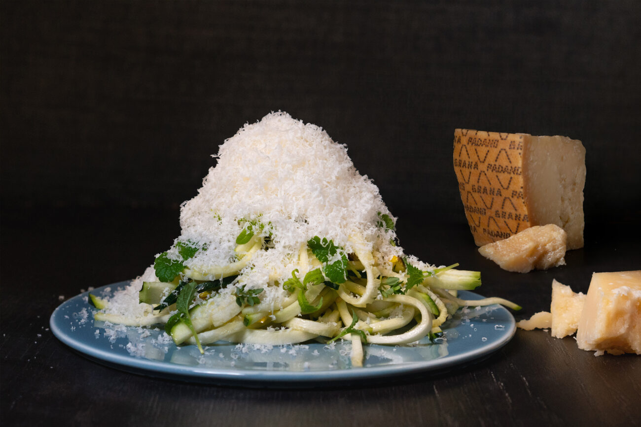 Salat af zucchini, ristede pistacier, pistacienøddeolie, citrusurter og revet Grana Padano